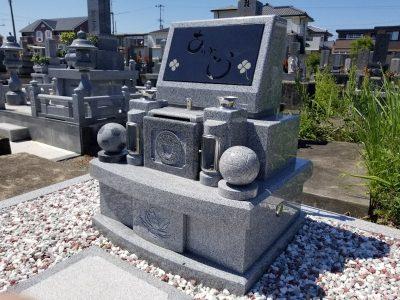 御影石のサッカーボールとバレーボールのオブジェがかざられた現代墓